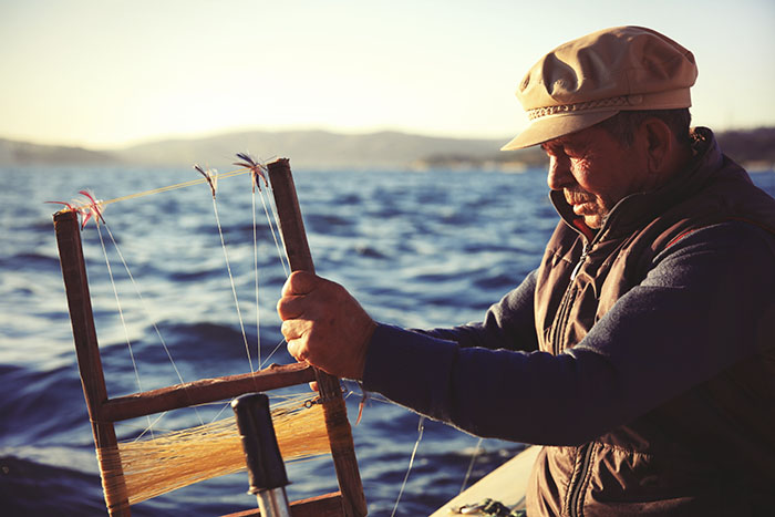Fisherman with small boats using traditional fishing methods for hunting bluefish and other fish species use similar methods for thousands of years in Istanbul.